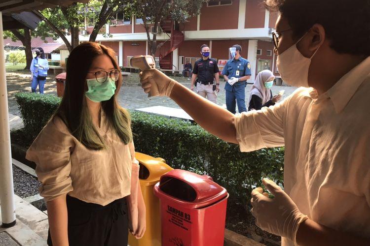 Rakita Nathania, siswi dari SMAK 5 Penabur, Kelapa Gading Jakarta sedang dicek suhu sebelum menempuh UTBK SBMPTN 2020 di Gedung VII Fakultas Ilmu Pengetahuan Budaya Universitas Indonesia (FIB UI), Depok, Jakarta, Minggu (5/7/2020) pagi. Ia menggunakan face shield saat mengerjakan soal UTBK SBMPTN 2020 demi memproteksi diri dari penularan Covid-19.