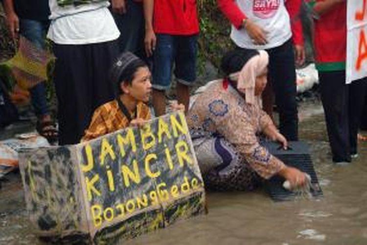 Puluhan warga Kampung Kincir, Desa Bojong Baru, RT 05 RW 06, Kecamatan Bojonggede, Kabupaten Bogor, sedang menggelar aksi teaterikal seperti membuang hajat dan mencuci baju, Selasa (23/6/2015). Aksi tersebut sebagai bentuk protes warga terhadap kondisi jalan yang rusak parah dan tak kunjung diperbaiki oleh Pemerintah Daerah Kabupaten Bogor. K97-14