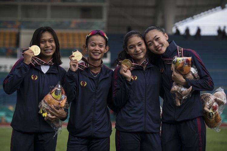 Tim pelari putri Jawa Barat Ulfa Silpiana (kanan), Erna Nuryamti (kedua kanan), Tyas Murtingsih (kedua kiri) dan Raden Roselin (kiri) memperlihatkan medalinya usai menang pada babak final Lari Estafet 4x100 meter Putri PON Papua di Stadion Atletik Mimika Sport Center, Kabupaten Mimika, Papua, Rabu (13/10/2021). Tim Jawa Barat meraih medali emas sekaligus memecahkan rekor PON dengan catatan waktu 45,67 detik, sementara tim Jawa Timur meraih medali perak dan tim DKI Jakarta meraih medali perunggu. ANTARA FOTO/Novrian Arbi/YU
