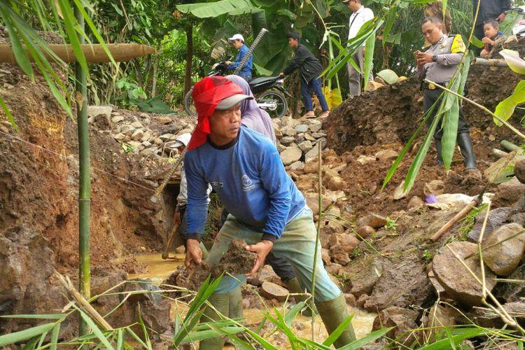 Warga bergotongroyong memperbaiki jalan putus di Desa Bencoy, Kecamatan Cireunghas, Sukabumi, Jawa Barat, Minggu(29/10/2017).
