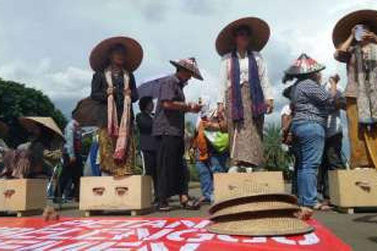 Sembilan petani perempuan yang kerap disebut Kartini pegunungan Kendeng, kembali menggelar aksi protes dengan mengecor kaki mereka dengan semen, di seberang Istana Negara, Rabu (13/4/2016). Mereka menolak keberadaan pabrik semen di wilayah Pegunungan Kendeng, Jawa Tengah, karena berdampak buruk pada kondisi lingkungan.