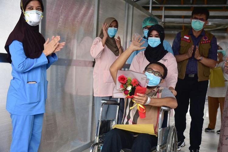 Pasien positif COVID-19 terakhir yang dirawat di RSUD Arifin Achmad (tengah) melambaikan tangan untuk berterima kasih kepada tenaga kesehatan saat proses pemulangan di Kota Pekanbaru, Riau, Minggu (31/5/2020). Pemerintah Indonesia menyatakan jumlah pasien sembuh dari COVID-19 hingga 31 Mei 2020 terus bertambah jadi 7.308 orang dari total kasus terkonfirmasi positif yang mencapai 26.473 orang, dan yang meninggal dunia 1.613 orang. ANTARA FOTO/FB Anggoro/aww.