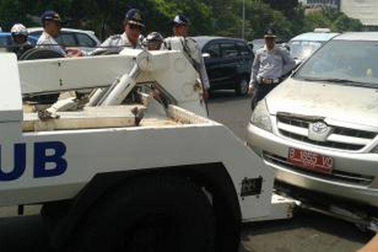 Sebuah mobil Toyota Innova berpelat merah diderek petugas dari Dinas Perhubungan dalam penertiban parkir liar di Jalan Gajah Mada, tepatnya di depan PN Jakarta Pusat, Selasa (9/9/2014).
