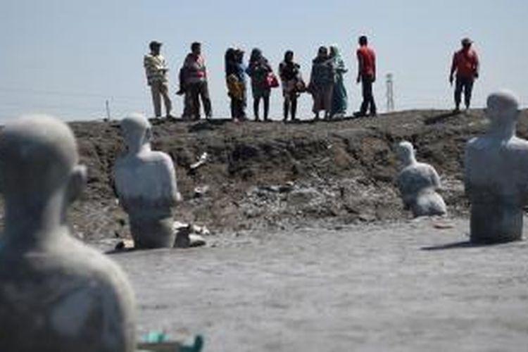Wisatawan berada di kolam lumpur Lapindo yang di pasangi instalasi berjudul Survivor di Desa Siring, Kecamatan Porong, Sidoarjo, Jawa Timur, Kamis (28/5/2015). HIngga saat ini masih menyisakan permasalahan ganti rugi warga yang menjadi korban.    Kompas/Bahana Patria Gupta (BAH)  28-05-2015