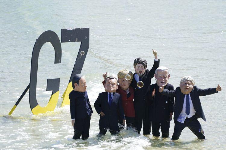 Para pengunjuk rasa berkepala raksasa yang menggambarkan pemimpin G7 berpose setelah demonstrasi di pantai di luar pertemuan G7 di St. Ives, Cornwall, Inggris, Minggu, 13 Juni 2021.