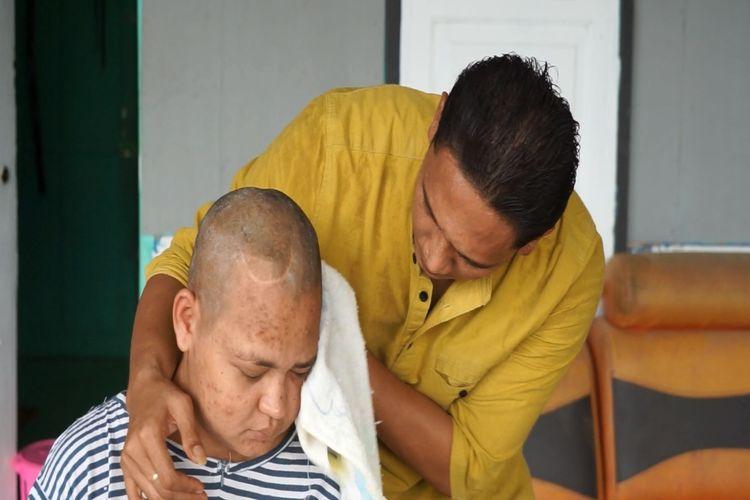T Reza Putra, sedang mendampingi istrinya Fitri Wahyuni (31) di rumah orangtuanya Desa Pusong Baru, Kecamatan Banda Sakti, Kota Lhokseumawe, Kamis (30/7/2020). (KOMPAS.com/MASRIADI )  Artikel ini telah tayang di Kompas.com dengan judul