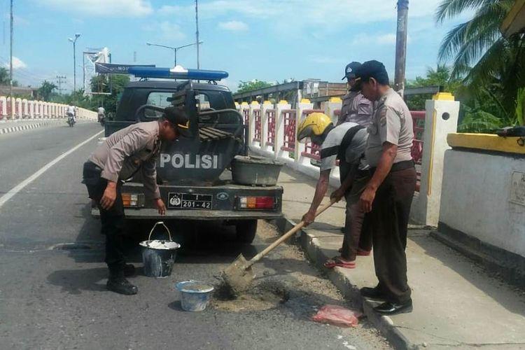 Tim Polsek Lhoksukon, Kabupaten Aceh Utara, menambal badan jalan yang berbulang di lintas nasional Medan-Banda Aceh, di Jembatan Lhoksukon, Kecamatan Lhoksukon, Kabupaten Aceh Utara,Senin (20/5/2019).