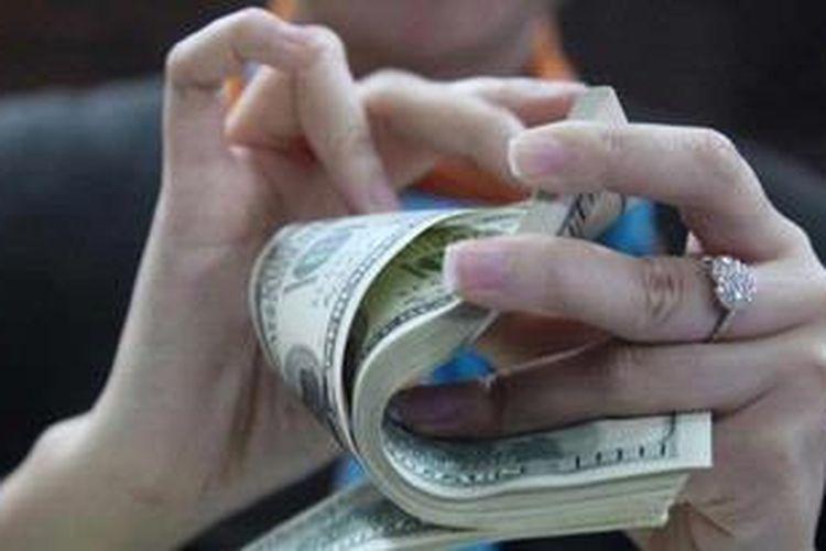 Pegawai menghitung uang dollar Amerika di Bank BNI Jakarta, Selasa (28/5/2013). Berdasar kurs tengah Bank Indonesia, rupiah ditutup Rp 9.810 per dollar Amerika atau melemah dibanding sehari sebelumnya Rp 9.792.