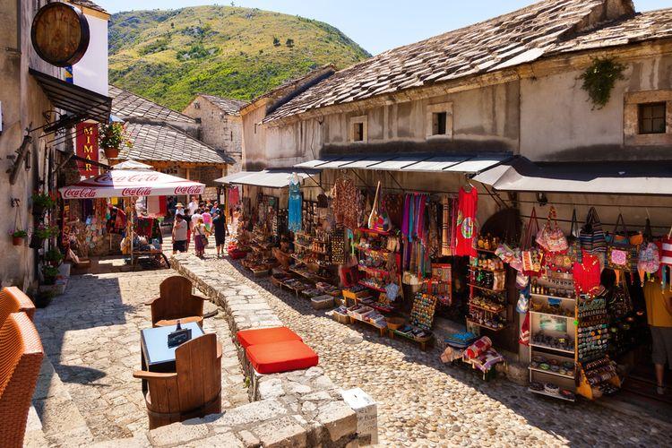 Jalanan di Old Town Mostar dengan latar belakang gunung dan jejeran toko suvenir serta kafe