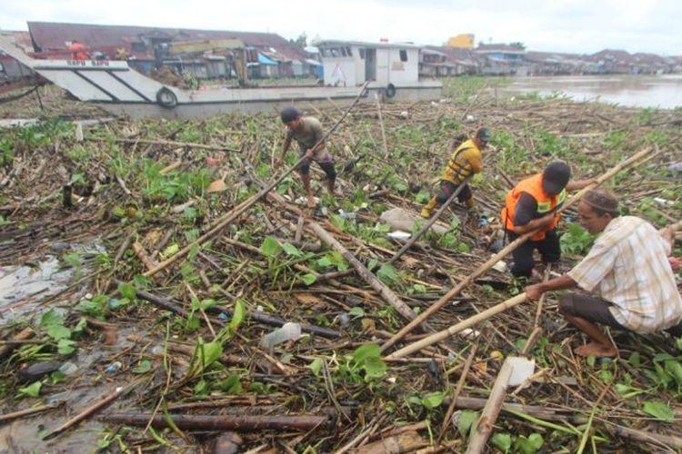 Petugas berusaha membersihkan sampah yang menutup sebagian permukaan Sungai Martapura di Kota Banjarmasin.