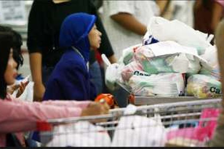 Pembeli bersiap membawa belanjaan mereka yang dibungkus kantong plastik di sebuah pasar swalayan di Jakarta, beberapa waktu lalu. Pemerintah berencana menerapkan pembatasan kantong plastik pembungkus untuk mengurangi sampah plastik yang sulit terurai.