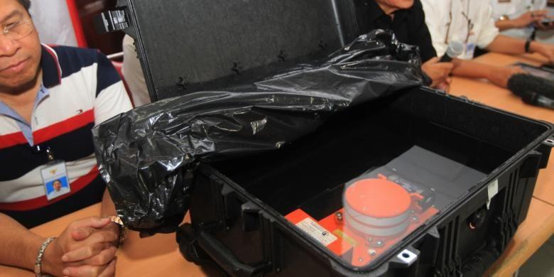 Petugas menunjukkan cockpit voice recorder (CVR) yang merupakan bagian kotak hitam pesawat AirAsia QZ8501 di Kantor Komite Nasional Keselamatan Transportasi, Jakarta, Selasa (13/1/2015). CVR tersebut salah satu bagian kotak hitam yang berisi percakapan pilot dan kopilot.