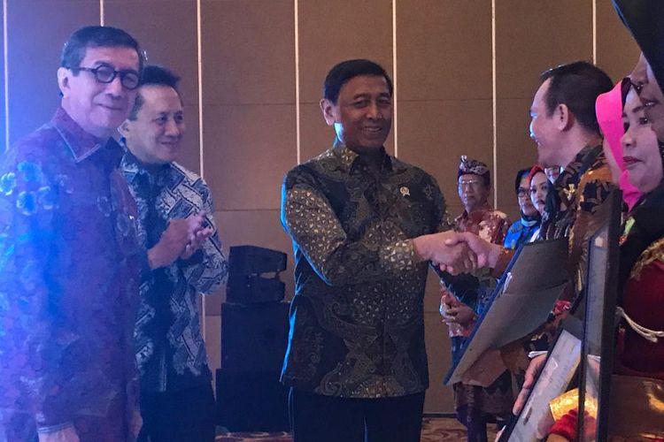 Menteri Koordinator bidang Politik, Hukum, dan Keamanan (Menko Polhukam) Wiranto, didampingi Menteri Hukum dan Hak Asasi Manusia (Menkumham) Yasonna Laoly, dan Kepala Bekraf Triawan Munaf, saat menyerahkan sertifikat, di Hotel JS Luwansa, Jakarta Selatan, Senin (8/4/2019).