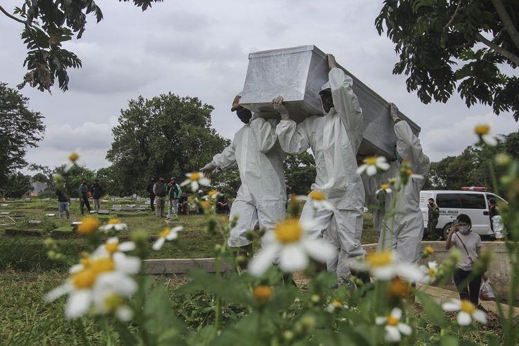 Petugas mengusung peti berisi jenazah yang meninggal dunia karena COVID-19 untuk dimakamkan di TPU Srengseng Sawah, Jakarta, Kamis (14/1/2021). Pemerintah Provinsi DKI Jakarta membuka area pemakaman untuk jenazah COVID-19 di TPU Srengseng Sawah karena Taman Pemakaman Umum (TPU) khusus COVID-19 telah penuh. ANTARA FOTO/Asprilla Dwi Adha/wsj.
