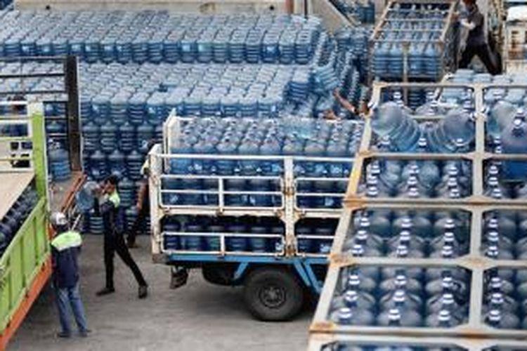 Karyawan perusahaan air minum dalam kemasan sedang bersiap mendistribusikan ratusan galon air ke dalam truk pengangkut.