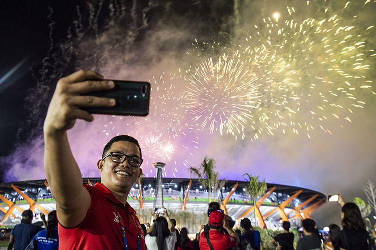 Seorang relawan melakukan swa foto dengan latar belakang kembang api saat penutupan SEA Games 2019 di Stadion Atletik New Clark City, Tarlac, Filipina, Rabu (11/12/2019). Pesta olahraga terbesar ke-30 di Asia Tenggara tersebut resmi ditutup dan Vietnam akan menjadi tuan rumah selanjutnya untuk SEA Games 2021.
