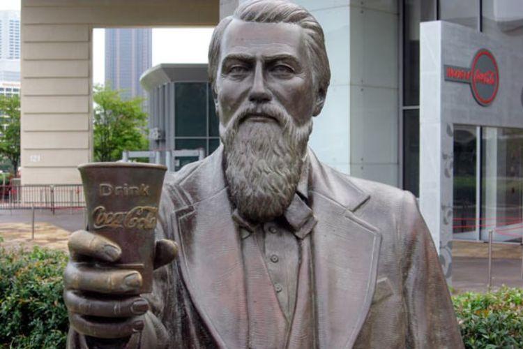 Patung John Pemberton memegang gelas Coca-Cola.