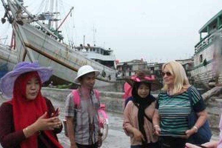 Turis kapal pesiar MS Rotterdam berbincang-bincang dengan penduduk di Pelabuhan Sunda Kelapa, Jakarta, Kamis (19/2/2015).