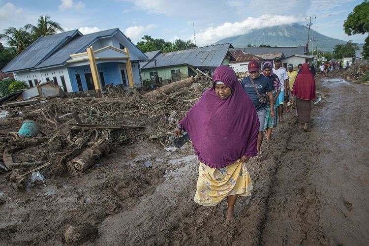 A number of local people in East Flores regency, East Nusa Tenggara province make their way through the muddy ruins of their homers after mudslides hit their home on Tuesday (6/4/2021). ANTARA FOTO/Aditya Pradana Putra/wsj.