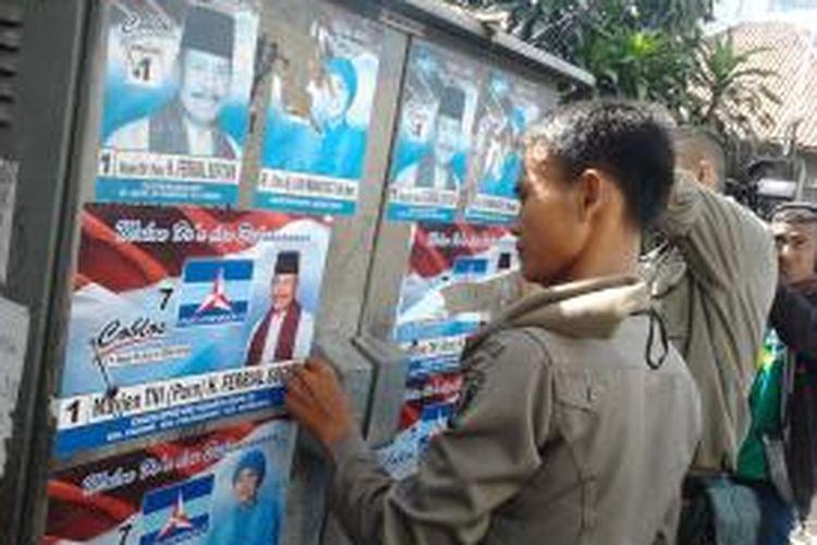 Petugas Satpol PP melakukan pencopotan atribut kampanye yang masih terpasang di hari kedua masa tengang Pileg. Pencopotan dilakukan serentak di seluruh wilayah Jakarta Timur. Senin (7/4/2014).