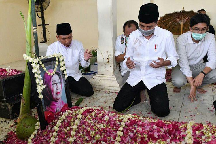 Presiden Joko Widodo berdoa di hadapan pusara almarhumah ibundanya, di kompleks pemakaman keluarga di Dukuh Mandu, Desa Nolligaten, Gondangrejo, Karanganyar, Jawa Tengah, Kamis (26/3/2020). Almarhum Ibunda Presiden Joko Widodo, Sujiatmi Notomiharjo meninggal dunia pada Rabu (25/3) pukul 16:45 WIB pada usia 77 tahun karena kanker.