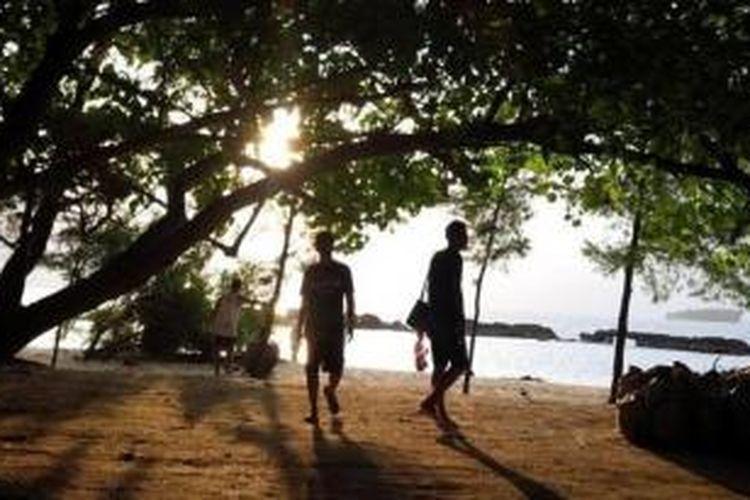 Wisatawan berjalan diantara pepohonan di Pulau Bulat, Sabtu (7/2/2015) sambil menikmati sunset. Di Pulau Bulat dan destinasi wisata lain di Kabupaten Kepulauan Seribu, ternyata tak memiliki fasilitas toilet yang baik.