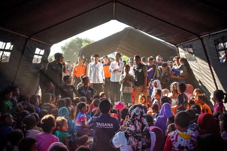 Presiden Joko Widodo (tengah) didampingi Gubernur NTB TGB Zainul Majdi (kedua kiri) berdialog dengan anak-anak korban gempa di Desa Madayin, Kecamatan Sambelia, Selong, Lombok Timur, NTB, Senin (30/7). Presiden Jokowi mengatakan pemerintah akan memberikan bantuan untuk perbaikan Rp 50 juta per rumah korban gempa yang mengalami kerusakan.