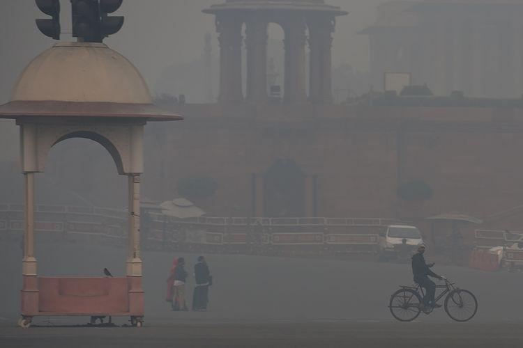 Warga beraktivitas di tengah kota Delhi, India yang tertutup kabut asap tebal yang berbahaya, Kamis (8/11/2018).