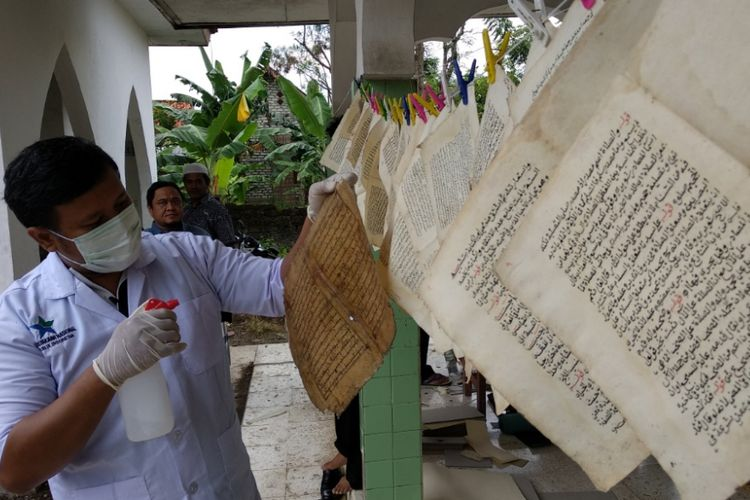 Petugas dari Perpustakaan Nasional sedang melakukan laminasi kitab berusia ratusan tahun di Pamekasan