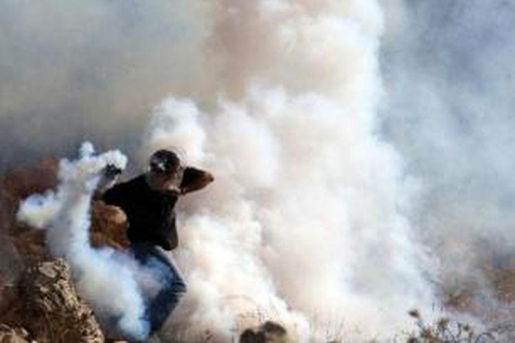 Seorang pengunjuk rasa Palestina, menutupi kepalanya dengan tas plastik untuk menghindari efek gas air mata yang dilepaskan pasukan Israel dalam bentrok di desa Nilin, West Bank pada 17 Desember 2010.