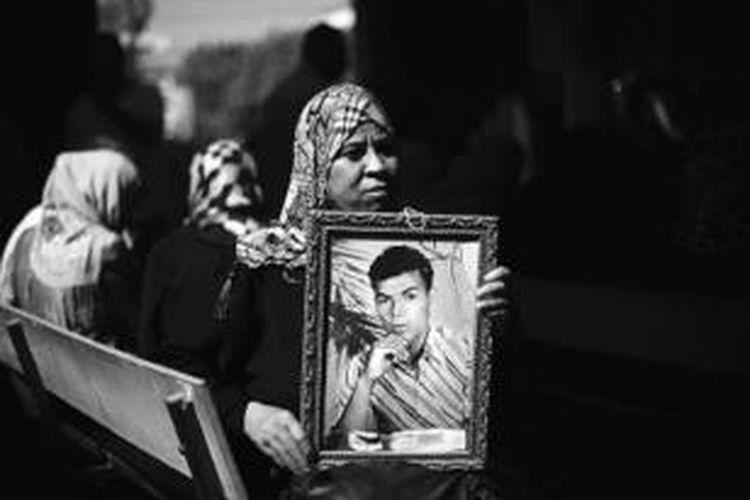 Seorang perempuan Palestina membawa foto saudaranya dalam pertemuan di depan kantor Palang Merah di Gaza City, Senin (12/8). Israel mengumumkan akan membebaskan 26 tahanan Palestina menjelang pembicaraan damai Palestina-Israel dilanjutkan, Rabu.  Namun Israel juga menyetujui pembangunan permukiman baru yang mengundang kemarahan Palestina.