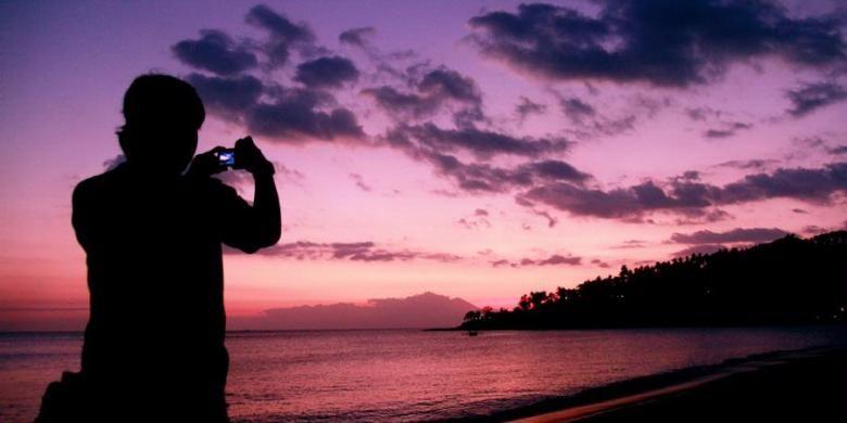 Wisatawan mengabadikan suasana senja di kawasan pantai Senggigi dari The Santosa Villas & Resort, Nusa Tenggara Barat, Kamis (7/7/2011).Objek wisata pantai di pulau Lombok masih menjadi tujuan utama para wisatawan dalam dan luar negeri.
