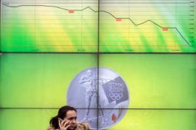 Nilai tukar mata uang Rusia, rubel, rontok di tengah penurunan harga minyak dunia, konflik Ukraina, dan ketidakpercayaan pasar terhadap kebijakan bank sentralnya yang menaikkan tinggi suku bunga acuan. Gambar diunggah pada Selasa (16/12/2014), memperlihatkan seorang perempuan berlatarkan papan kurs di depan bank terbesar di Rusia.