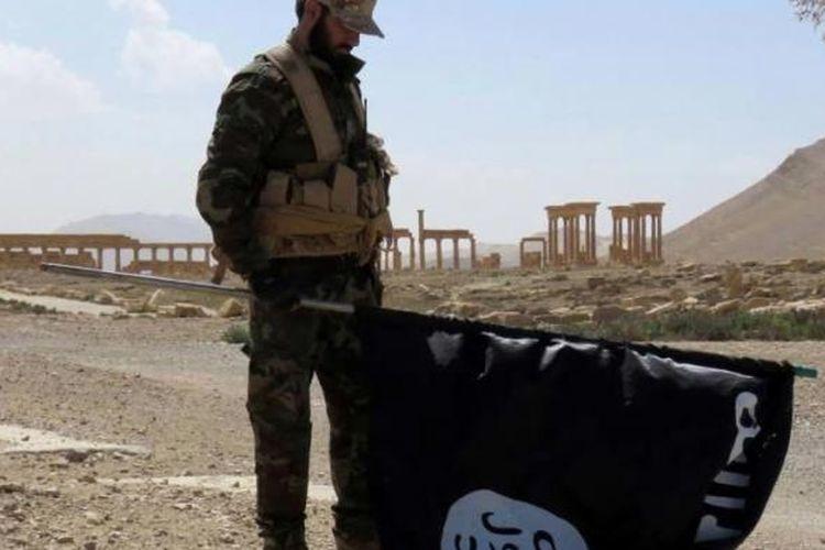 Seorang anggota pasukan pemerintah Suriah memegang bendera ISIS saay berada di jalan kota tua Palmyra yang direbut kembali dari tangan ISIS, Minggu (27/3/2016).