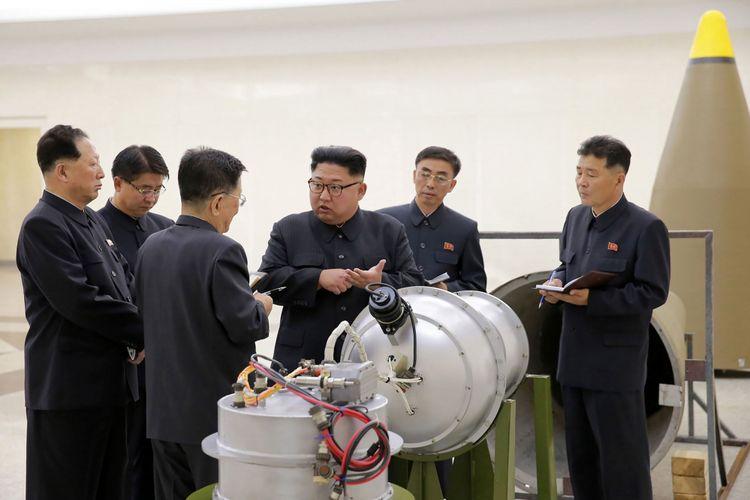 Foto tanpa tanggal yang dikeluarkan oleh kantor berita Korea Utara, KCNA, pada 3 September 2017, memperlihatkan pemimpin Korut Kim Jong Un (tengah) sedang melihat pipa logam di tempat yang tak diketahui.