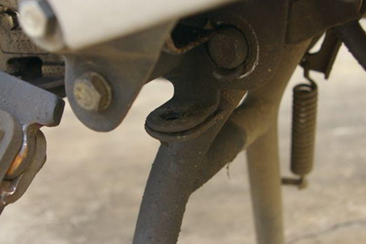 Lubang gembok pada standar tengah motor untuk pengaman.