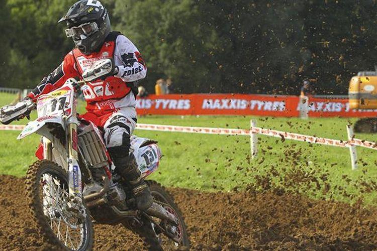 Pebalap motocross memacu motornya dalam balapan.