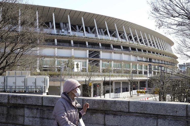 Seorang pejalan kaki melintas di National Stadium, lokasi digelarnya seremoni pembukaan dan penutupan Olimpiade 2020 Tokyo, Kamis (27/2/2020).
