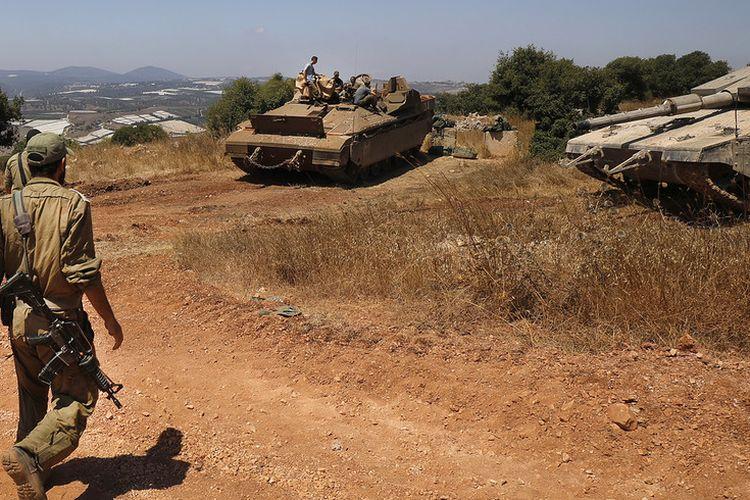 Tentara Israel berjalan dengan tank Merkava dan kendaraan angkut personel Namer dekat kota Avivim, di utara Israel berbatasan dengan Lebanon pada 23 Juli 2020.