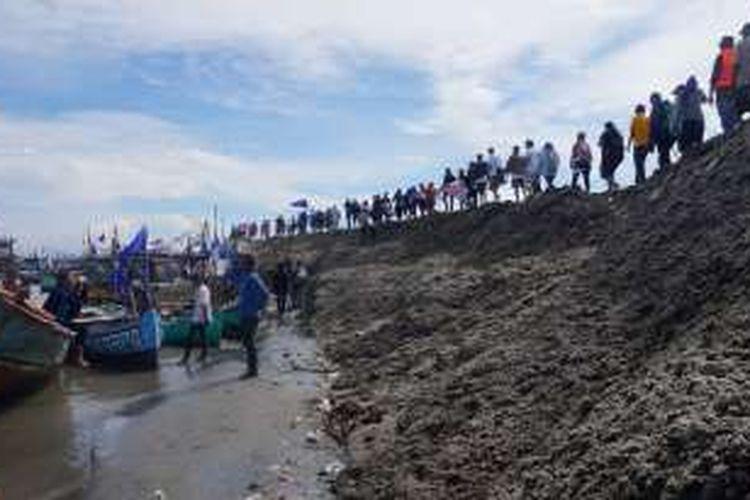 Warga berbaris di gunungan pasir Pulau G, saat melakukan aksi penyegelan pulau, Minggu (17/4/2016). Aksi yang diikuti ratusan warga pesisir Jakarta ini merupakan bentuk penolakan reklamasi Teluk Jakarta yang tengah berlangsung.