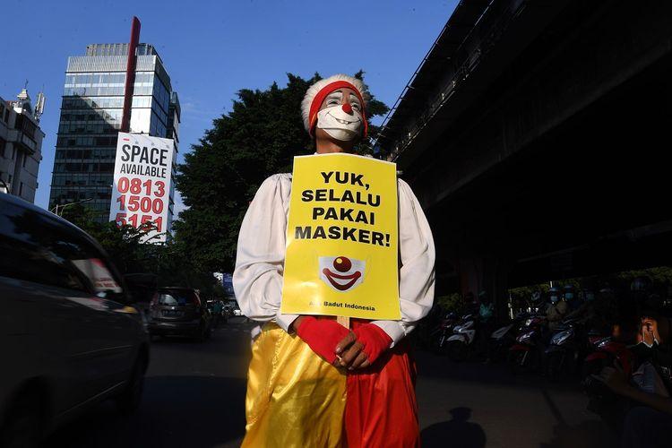 Seorang anggota komunitas Aku Badut Indonesia (ABI) melakukan aksi dengan mambawa poster di kawasan Fatmawati Jakarta, Senin (12/7/2021). Aksi tersebut untuk mengajak masyarakat menerapkan protokol kesehatan untuk mencegah penyebaran COVID-19 yang terus meningkat. ANTARA FOTO/Wahyu Putro A/foc.