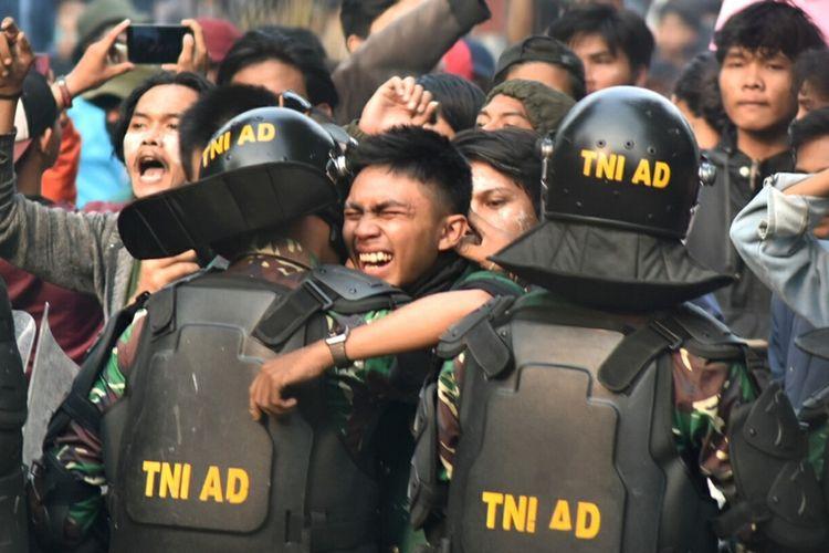 Aksi massa unjuk rasa di Gedung DPRD Jawa Barat, Kota Bandung, Jawa Barat, berakhir ricuh, Selasa (24/9/2019). Momen emosional saat salah seorang mahasiswa merangkul anggota TNI sambil menangis.