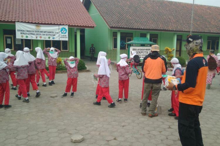 Petugas BPBD Kabupaten Magelang membagikan masker di sekolah-sekolah yang terdampak abu vulkanik Gunung Merapi, Kamis (24/5/2018) pagi.