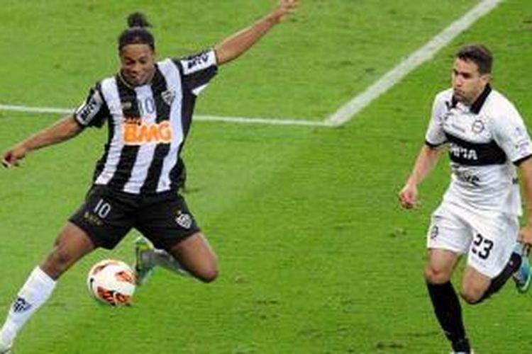 Playmaker Atletico Mineiro, Ronaldinho (kiri), memperlihatkan aksi ketika mengontrol bola di depan pemain Olimpia Paraguay, Jorge Baez, di leg kedua final Copa Libertadores Mineirao stadium, Brasil, Rabu (24/7/2013). Di leg kedua ini Mineiro menang 2-0 sehingga agregat menjadi 2-2, dan dilanjutkan dengan babak adu penalti yang dimenangkan Mineiro dengan skor 4-3.