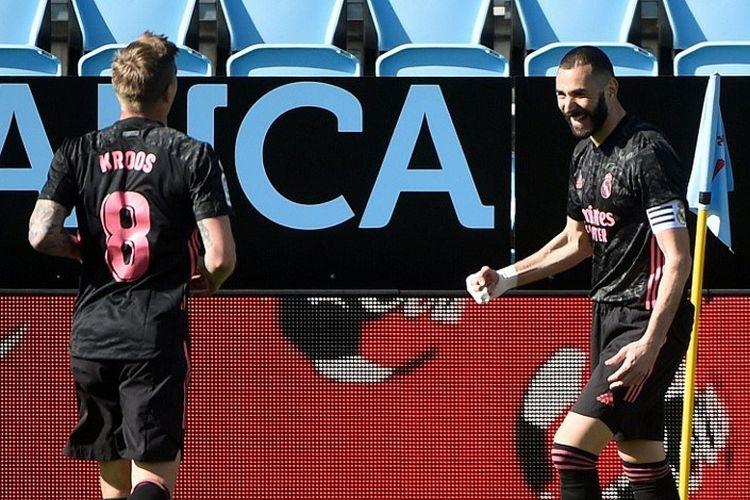 Bomber Real Madrid, Karim Benzema (kanan), berselebrasi setelah mencetak gol dalam pertandingan La Liga melawan Celta Vigo di Stadion  Balaidos, Sabtu (20/3/2021).