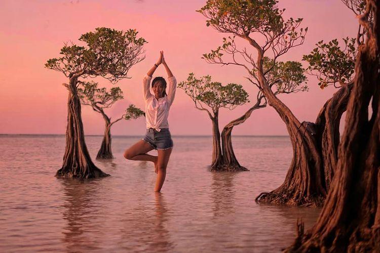 Seorang pengunjung berfoto dengan latar pohon menari di Pantai Walakiri, Pulau Sumba, Nusa Tenggara Timur (NTT).