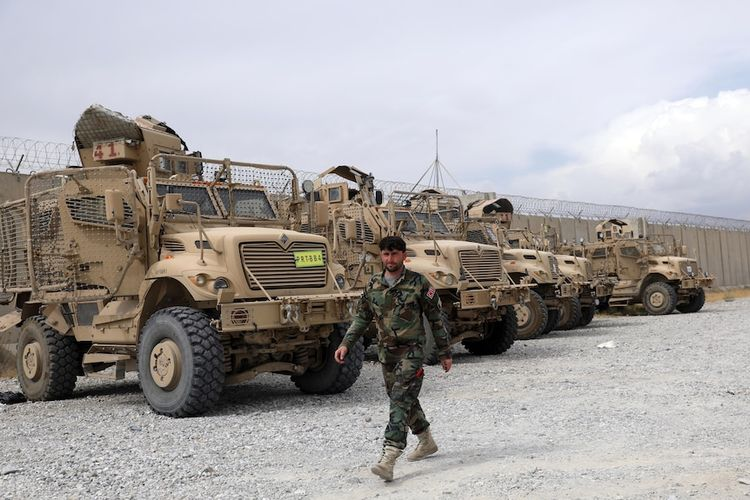 Seorang tentara Afghanistan dengan latar belakang kendaraan militer anti ranjau yang ditinggalkan oleh tentara AS di Bagram.