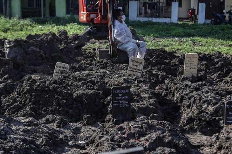 Pemakaman Covid-19  Sumber gambar, Antara foto Keterangan gambar,  Petugas pemakaman beristirahat usai memakamkan jenazah dengan protokol COVID-19 di TPU Selapajang, Kota Tangerang, Banten, Jumat (2/7/2021).