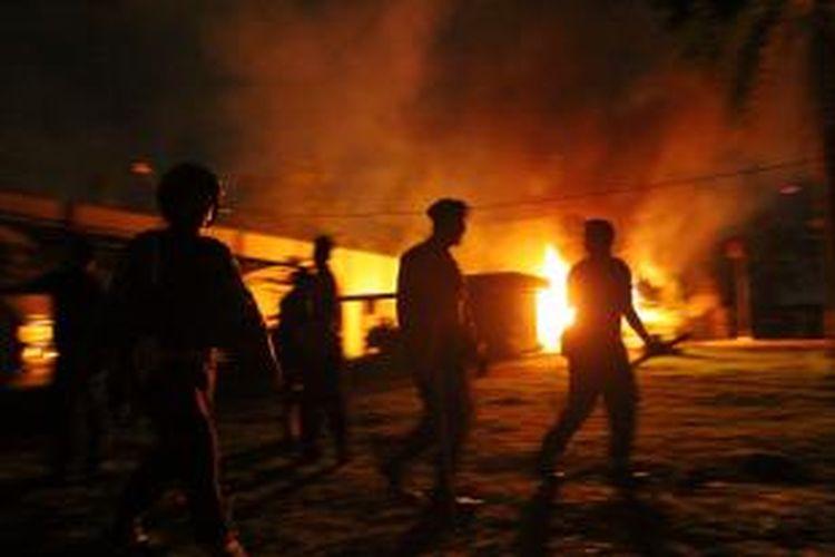 Polisi berjaga-jaga di kantor Lembaga Pemasyarakatan (Lapas) Klas I Tanjung Gusta, Medan, yang terbakar, Kamis (11/7/2013) malam. Lapas diduga dibakar sekelompok narapidana akibat adanya pemadaman listrik dan matinya air PDAM dalam Lapas. Diduga sekitar 300 napi berhasil kabur.