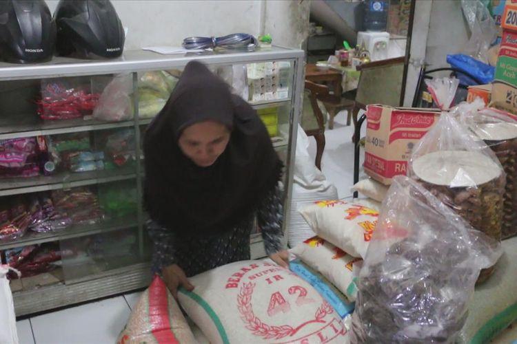 Titin Sopiatin (52) pemilik warung menunjukan dua buah karung beras yang masing-masing berisi 25 kilogram di warungnya, Pasar Celancang, Desa Purwawinangun, Kecamatan Suranenggala, Kabupaten Cirebon, Jumat (5/7/2019).